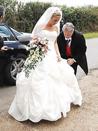 English toastmaster assisting a bride with her wedding dress